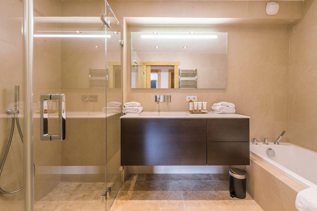 Beige bathroom with shower and bathtub at Omaroo II luxury chalet in Morzine