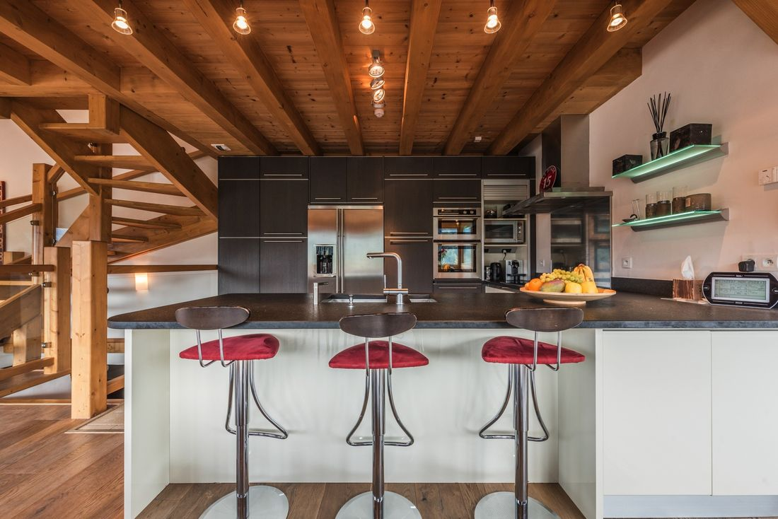 Black and white open kitchen with red bar stools at Omaroo I luxury chalet in Morzine