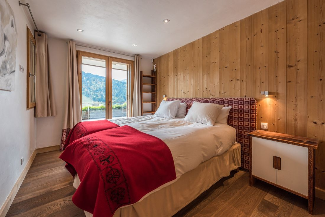 Two single beds with a red blanket at Omaroo I luxury chalet in Morzine