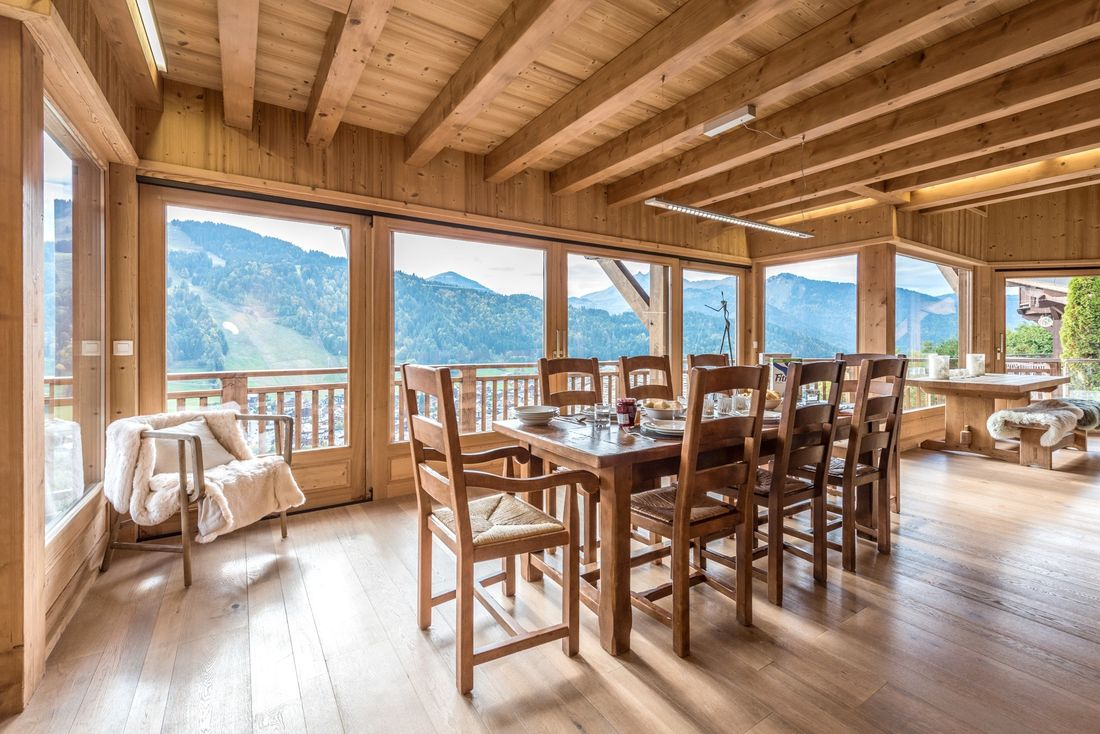 Wooden dining table and armchair with views over the Alps at Omaroo II luxury chalet in Morzine