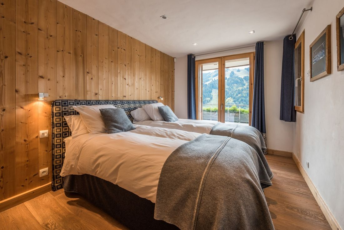 Two single beds and a wooden wall at Omaroo I luxury chalet in Morzine