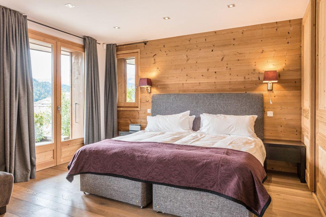 Grey double bed with purple blanket at Omaroo II luxury chalet in Morzine