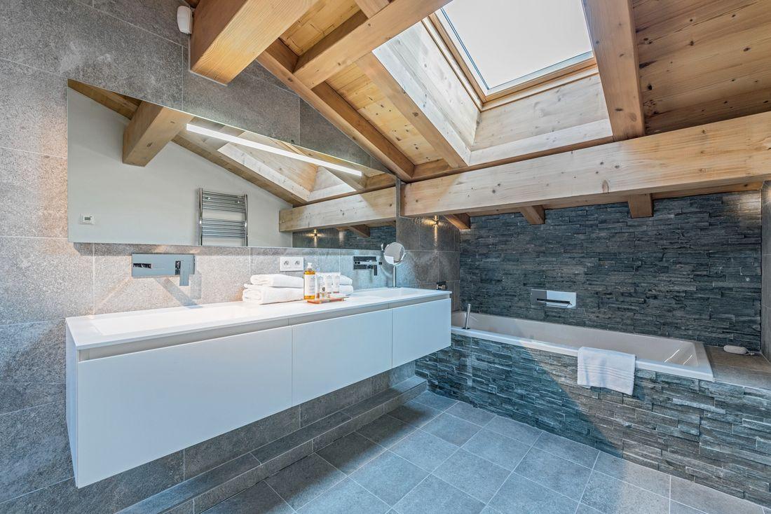 Stone bathroom with bathtub and roof window at Omaroo II luxury chalet in Morzine