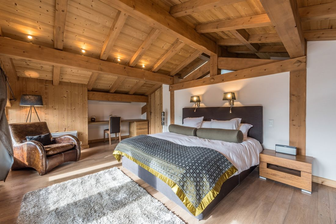 Wooden double bedroom with a brown leather armchair at Omaroo II luxury chalet in Morzine