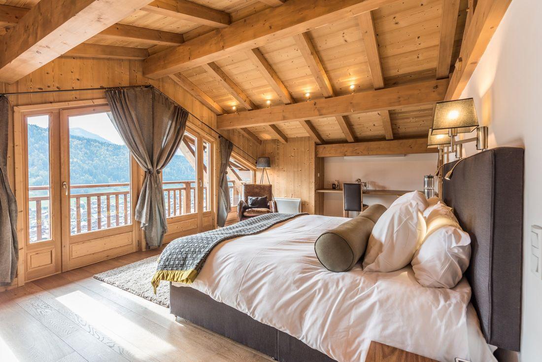Wooden double bedroom with Alps views at Omaroo II luxury chalet in Morzine