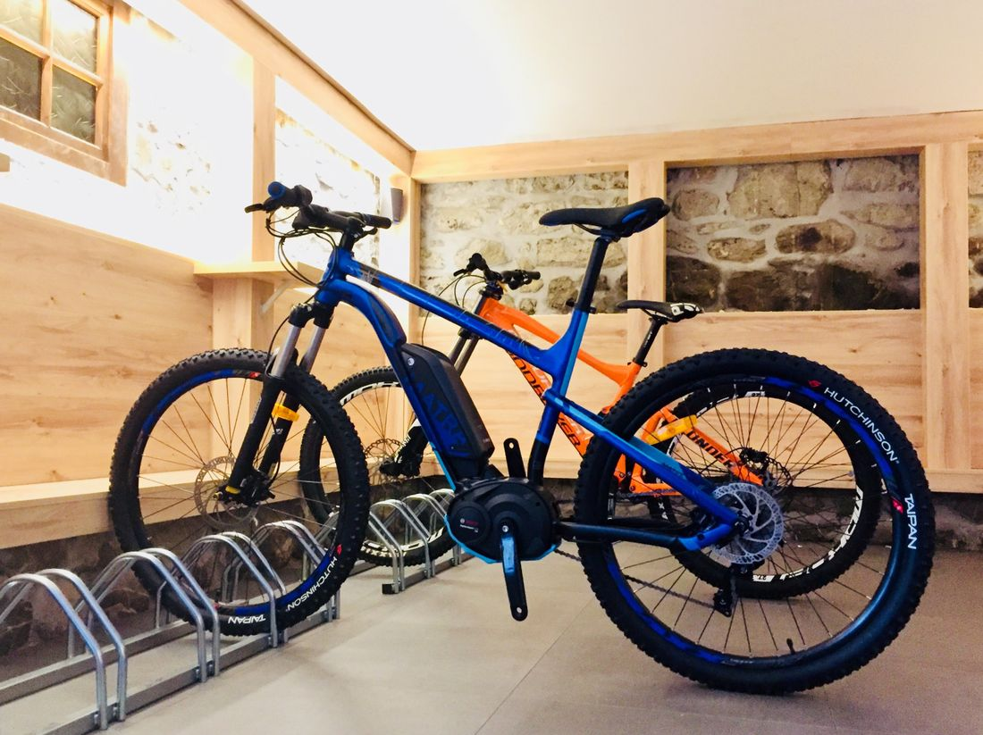Orange and blue bikes in the bike storage of Ayan accommodation in Morzine