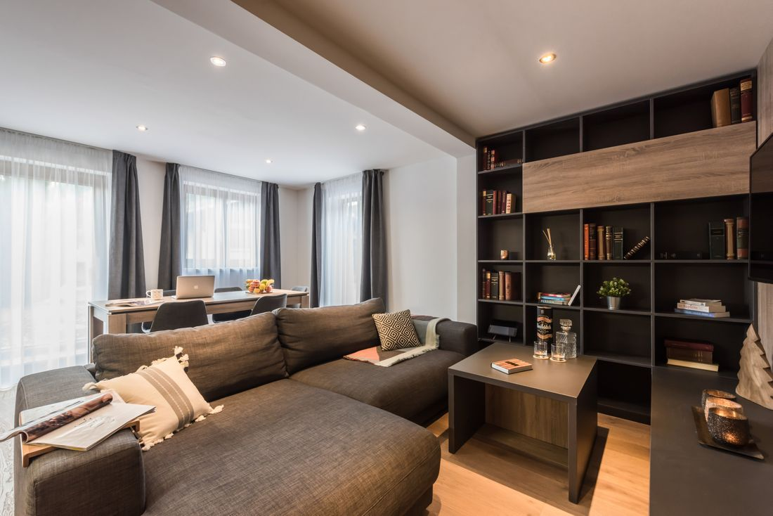 Modern living room with grey couch at Lovoa accommodation in Morzine