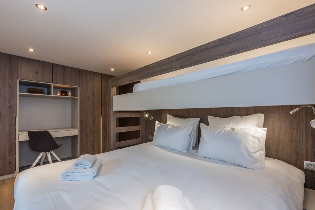 Wooden double bedroom with bunkbed and desk at Sugi accommodation in Morzine