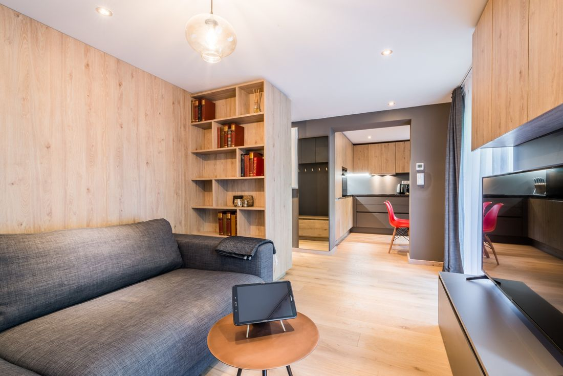 Wooden living room with dark grey couch at Karri accommodation in Morzine