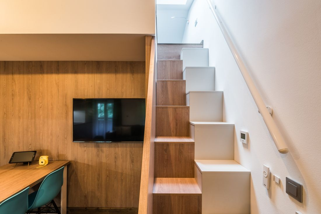 Flat-screen tv and wooden stairs at Kauri accommodation in Morzine