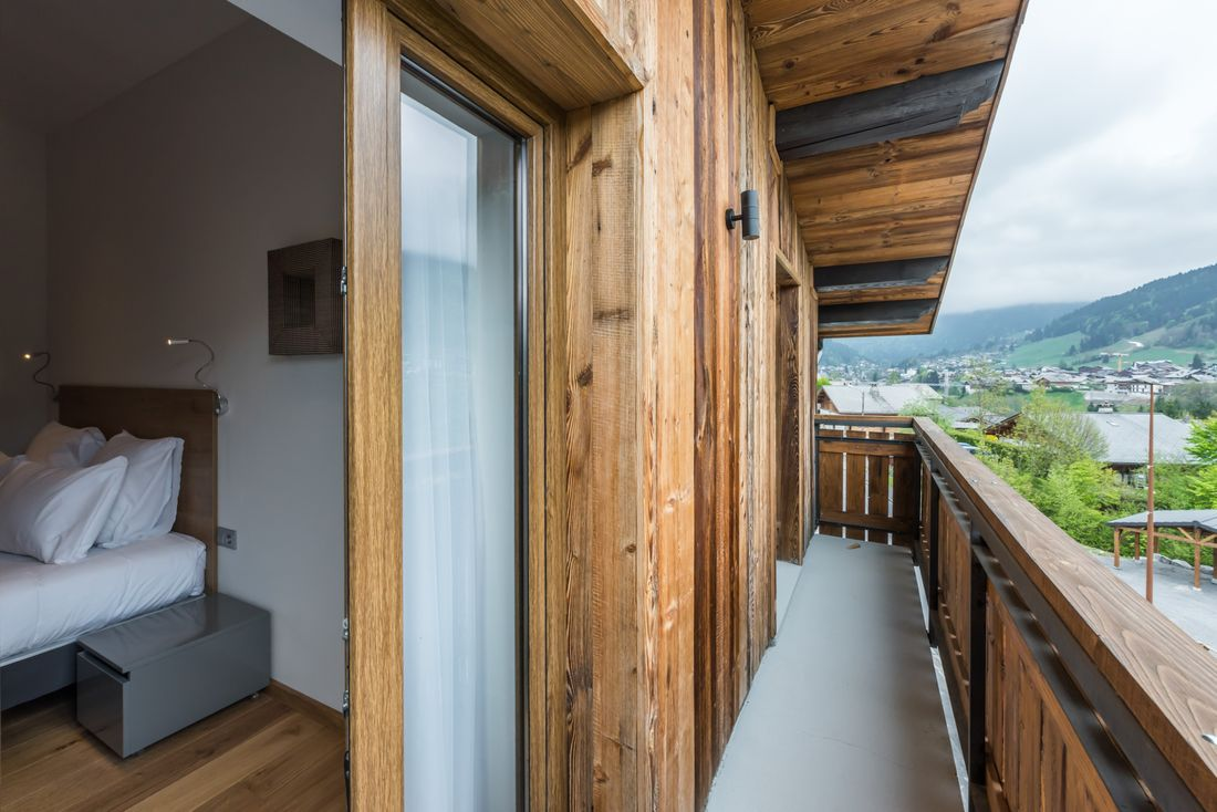 Bedroom with mountain view balcony at Agba accommodation in Morzine