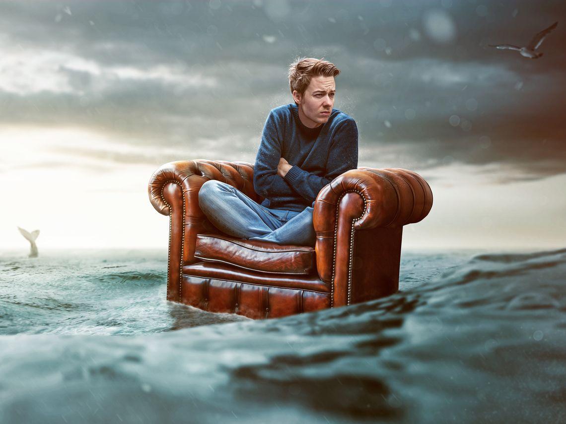 frierender Mann sitzt auf schwimmenden Sessel im stürmischen Meer