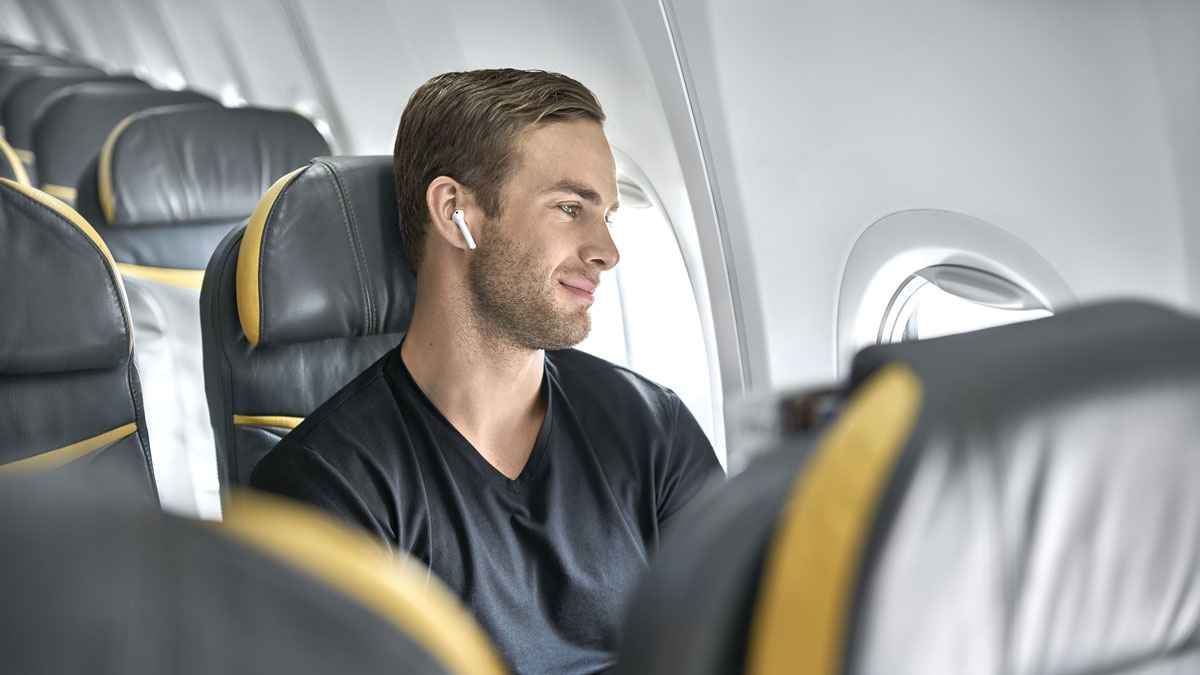 Guy On Plane With Noise Cancelling Earbuds