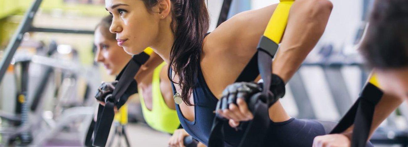kelett-Muskulatur: Frau trainiert an TRX Bändern Muskelanteil und Bewegungsapparat