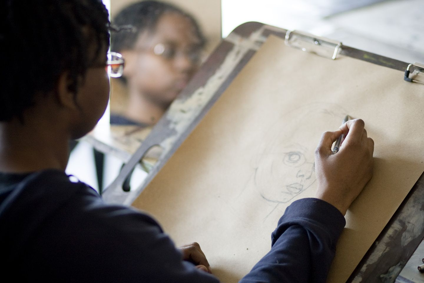 A student drawing on a brown piece of paper with pencil and looking into a mirror
