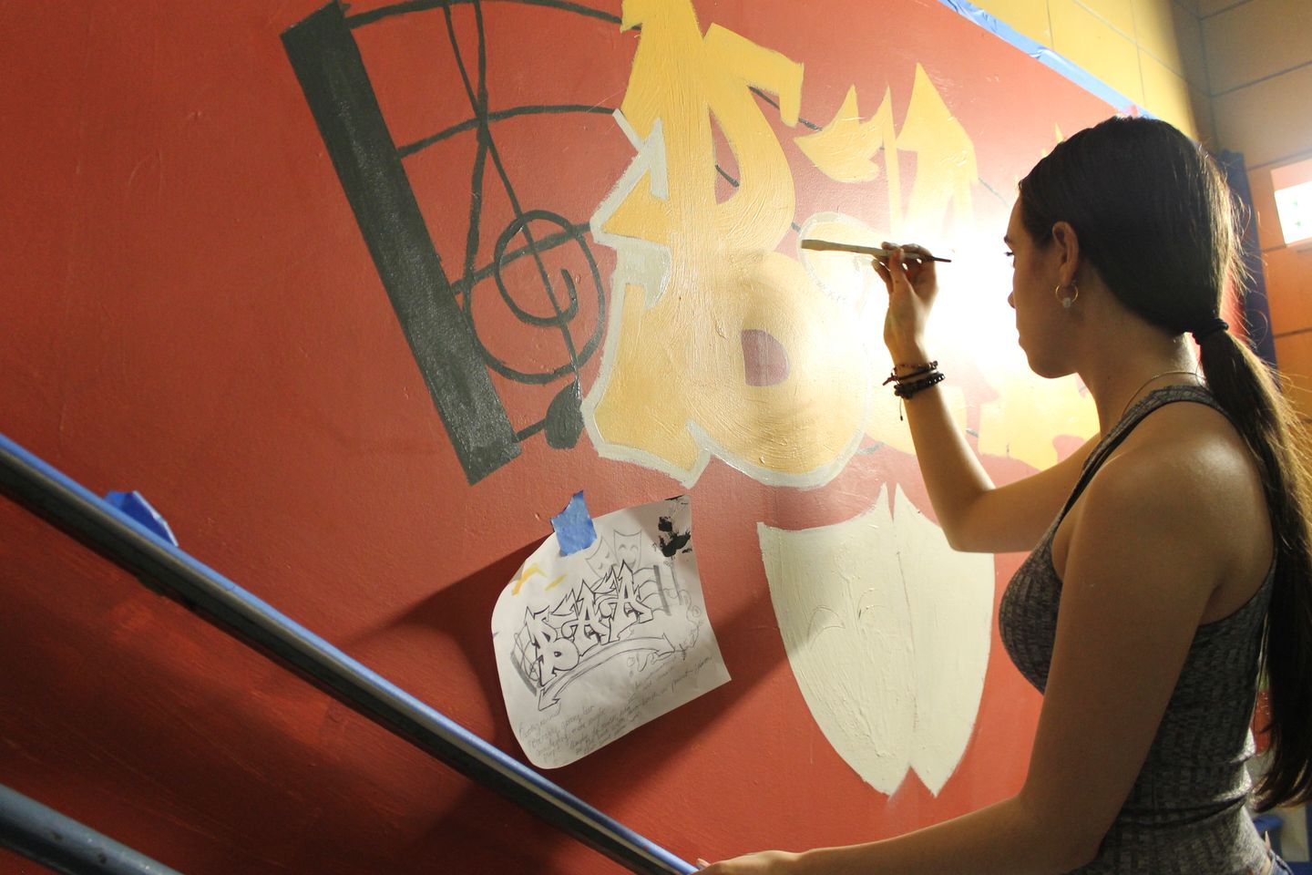 Girl in a stairwell painting the wall