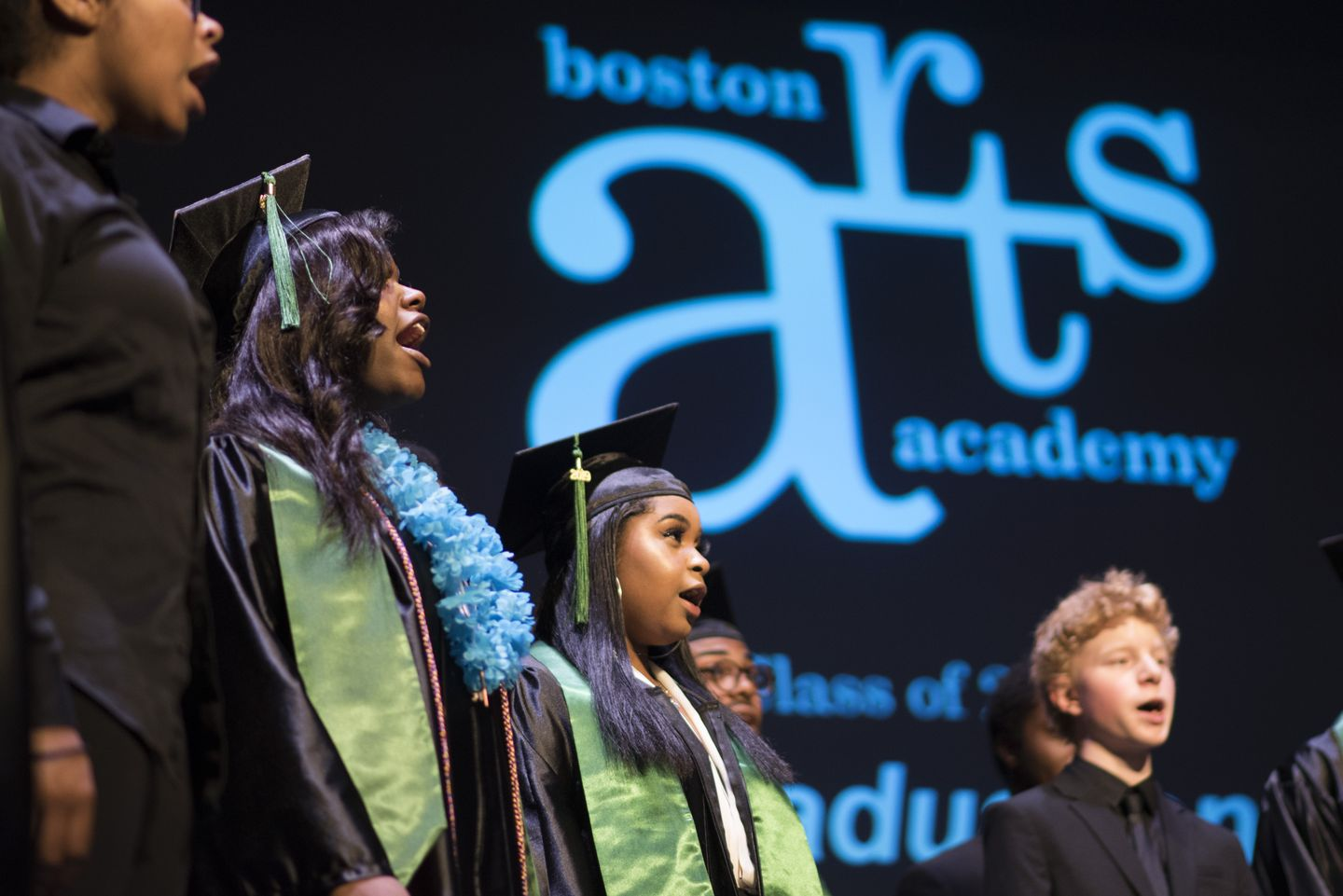 A group of young people in graduation caps singing in front of a banner with the Boston Arts Academy logo