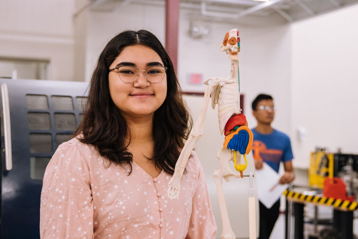A female student in front of a scale model of a human skeleton