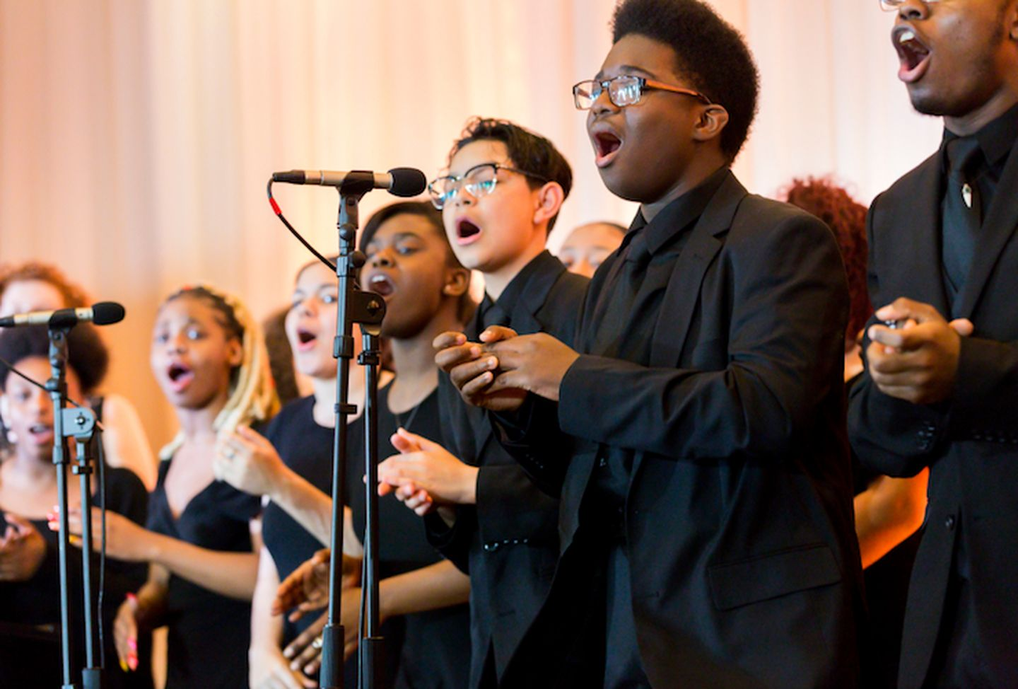 A bunch of teens singing together for a music performance.