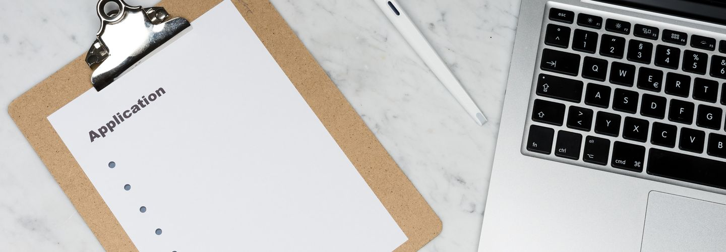 A picture of a clipboard, pen, and laptop from above on a white marble table.