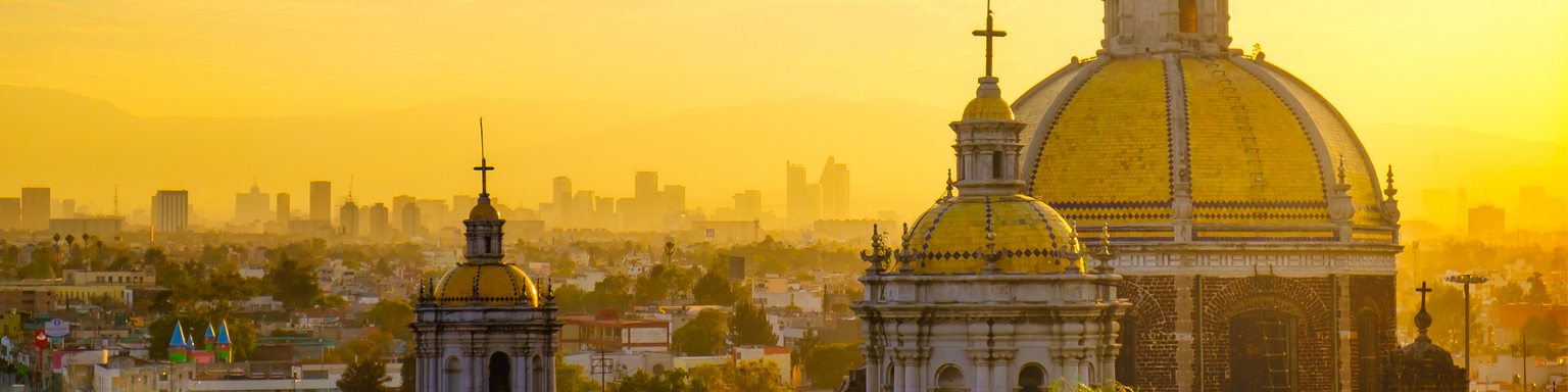 Scenic view at Basilica of Guadalupe with Mexico City skyline at sunset