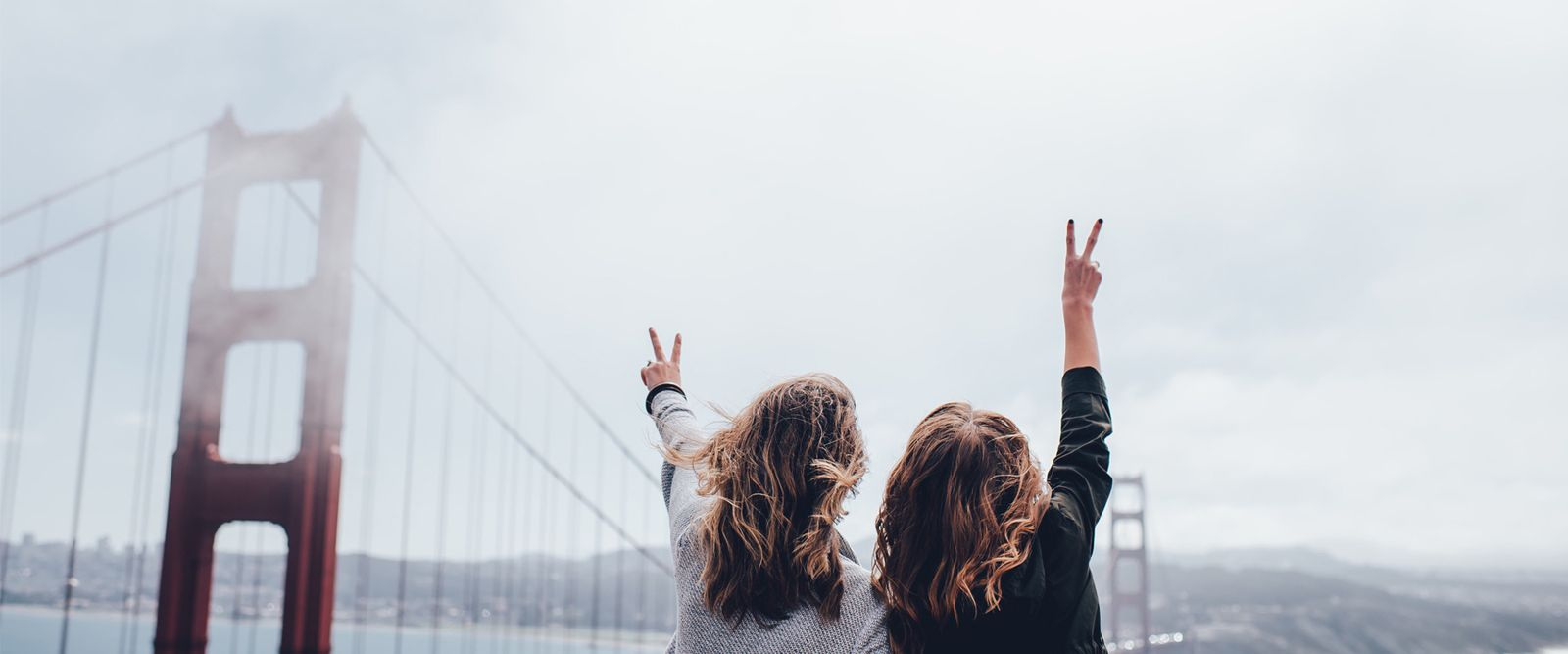 two girls cheering in front of a bridge