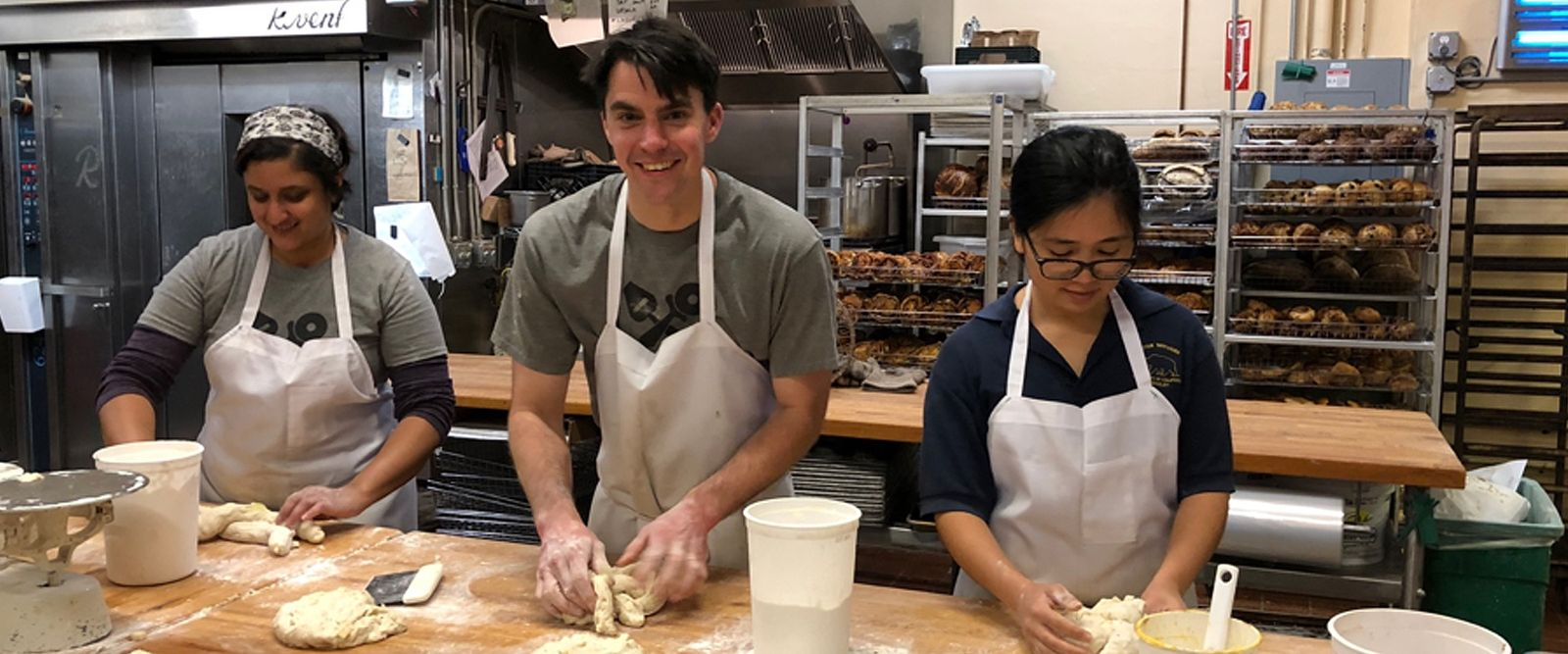 two women and one man in a bakery kitchen making bread