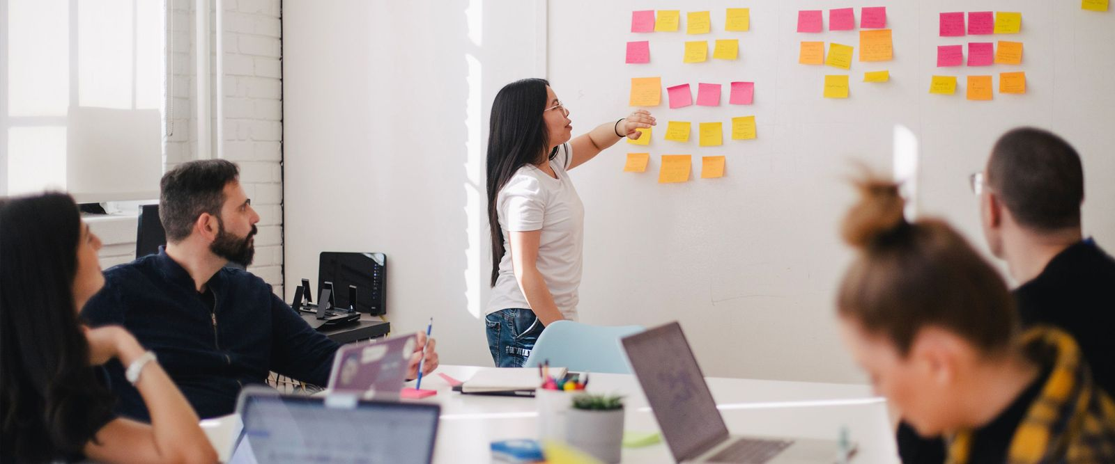 Workshop situation in front of a white wall with sticky notes
