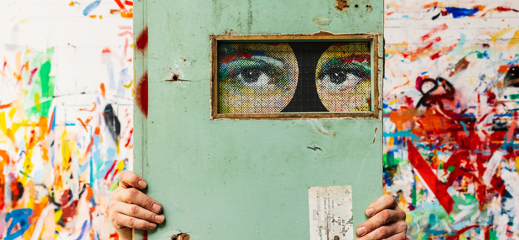a hand emerges from either side of a pale green door, through a hole in which two painted eyes are visible.