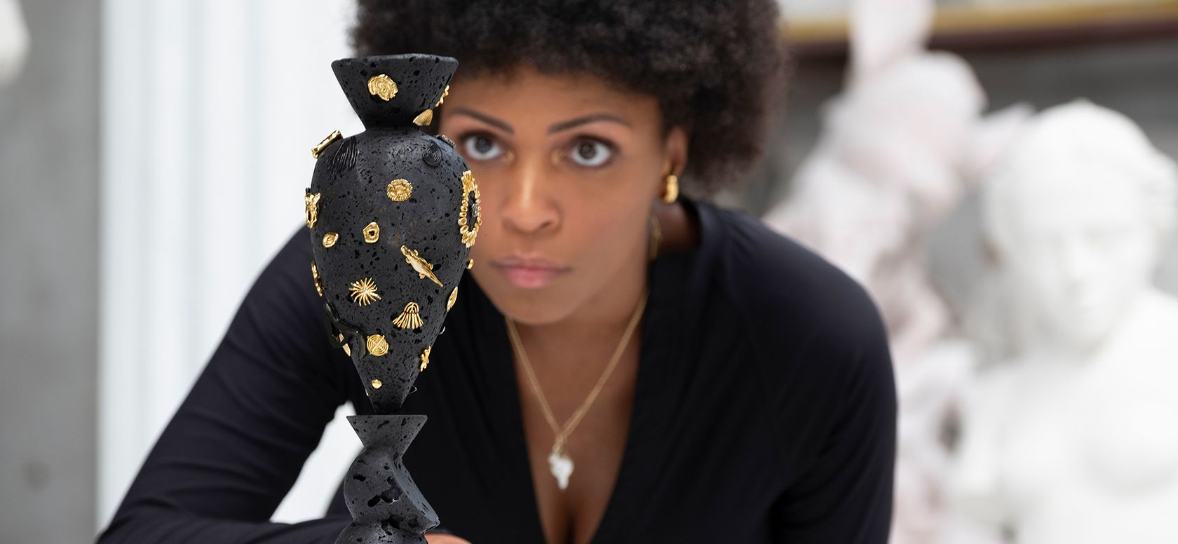 artist wearing gold jewellery inspects a black basalt sculpture from behind a white marble table