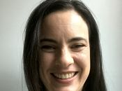 A headshot of Amy with an energetic smile in front of a grey background.
