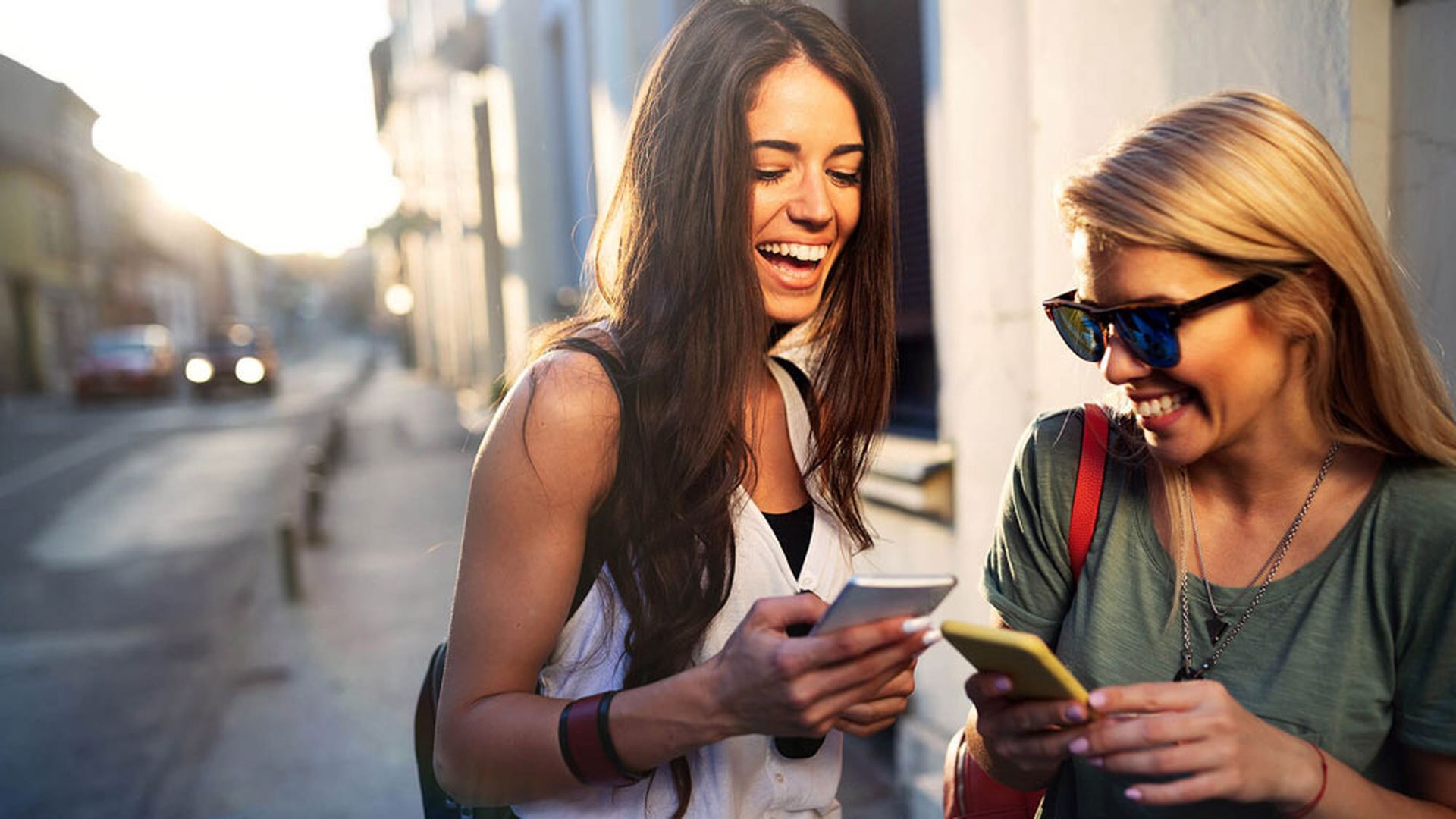 LINK Mobility -   zwei junge Frauen unterhalten sich und benutzen ihre Smartphones