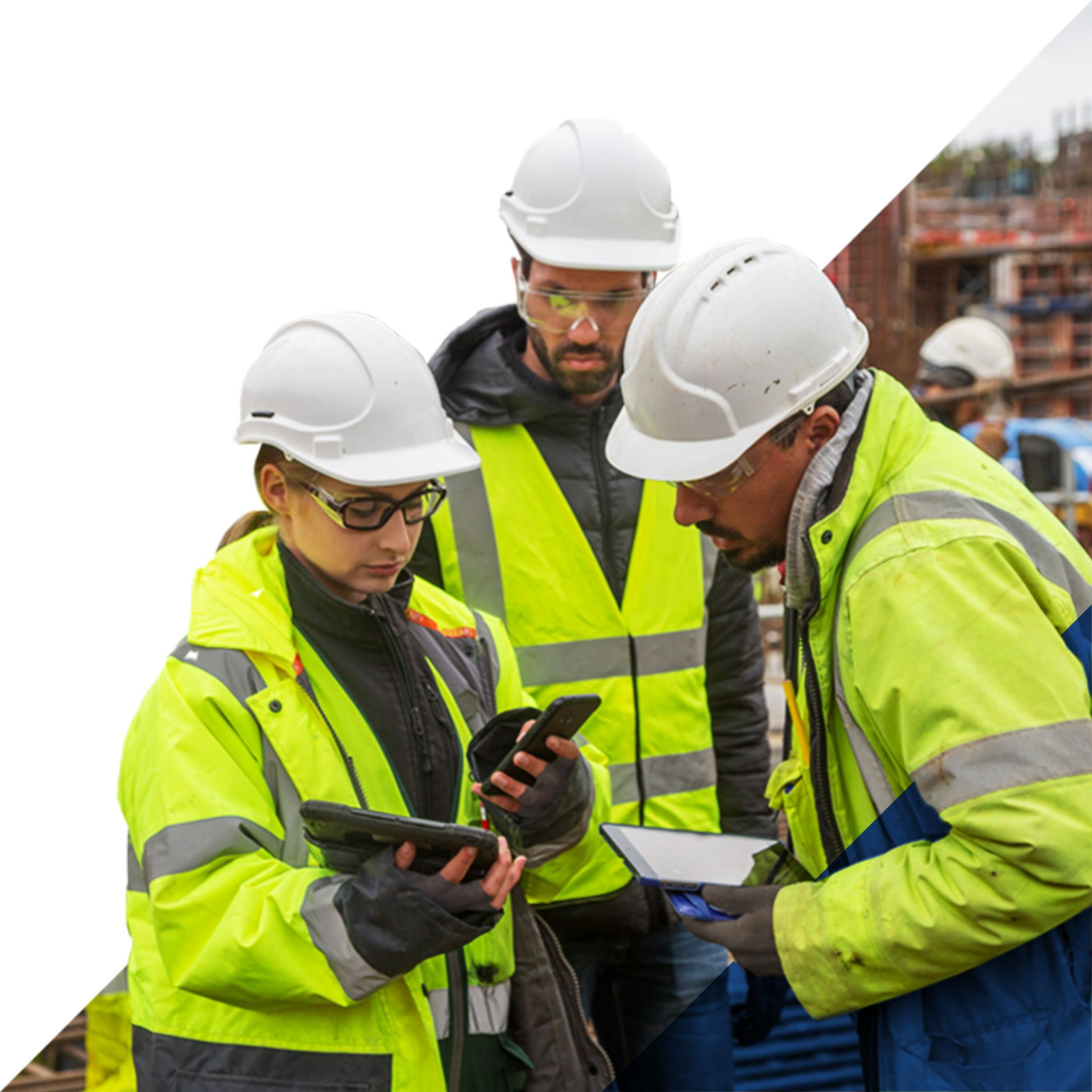 Three site construction workers looking at data on mobile devices and tablets.