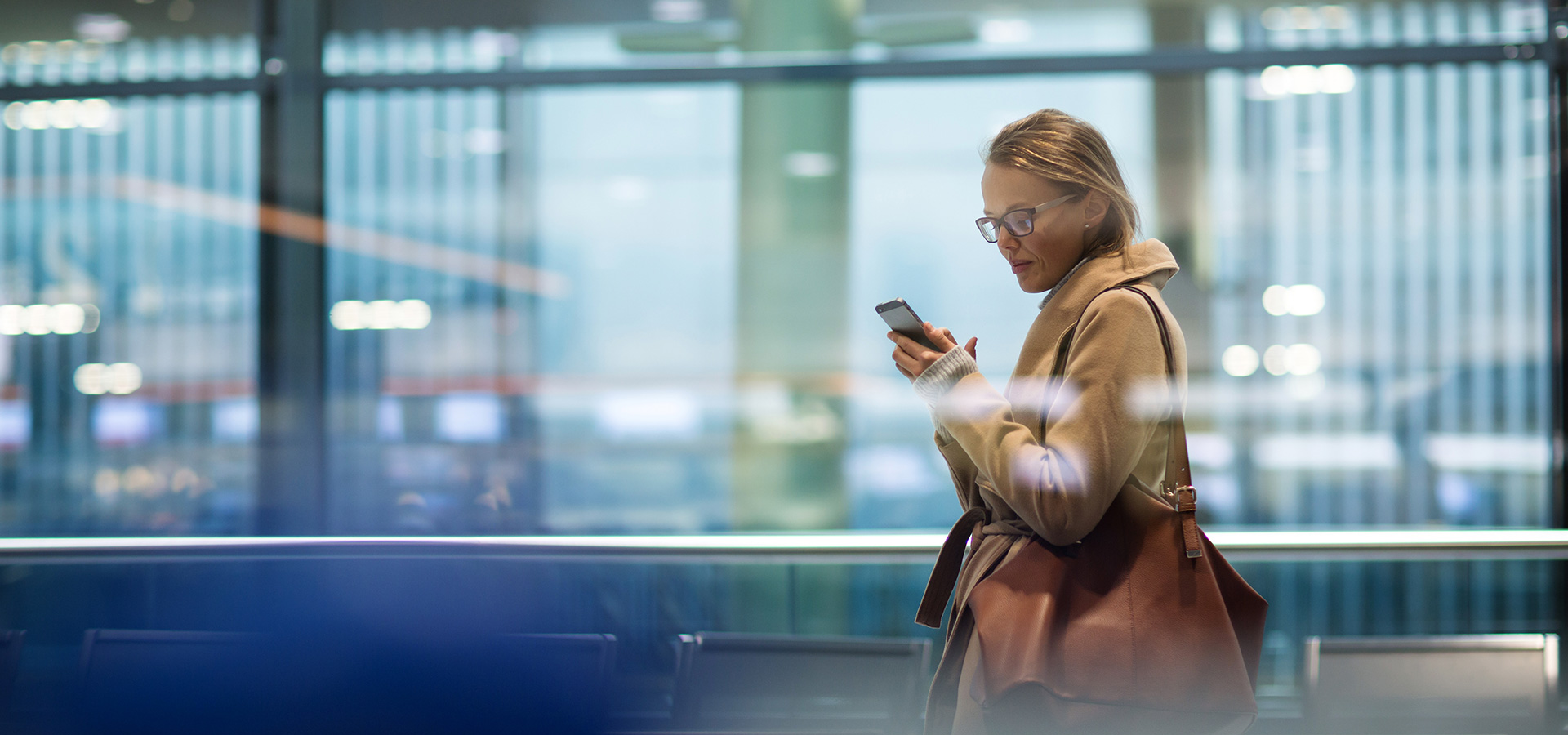LINK Mobility - Frau am Flughafen liest eine Nachricht auf ihrem Smartphone