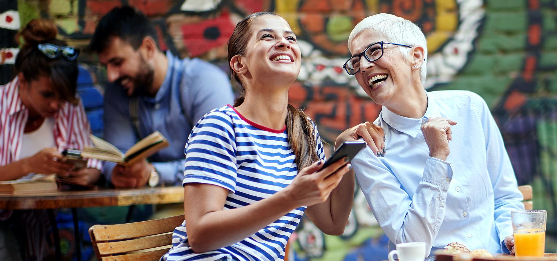 LINK Mobility - Großmutter und Enkelin sitzen im Freien in einem Cafe und lachen gemeinsam, während die jüngere Dame ihr Smartphone nutzt