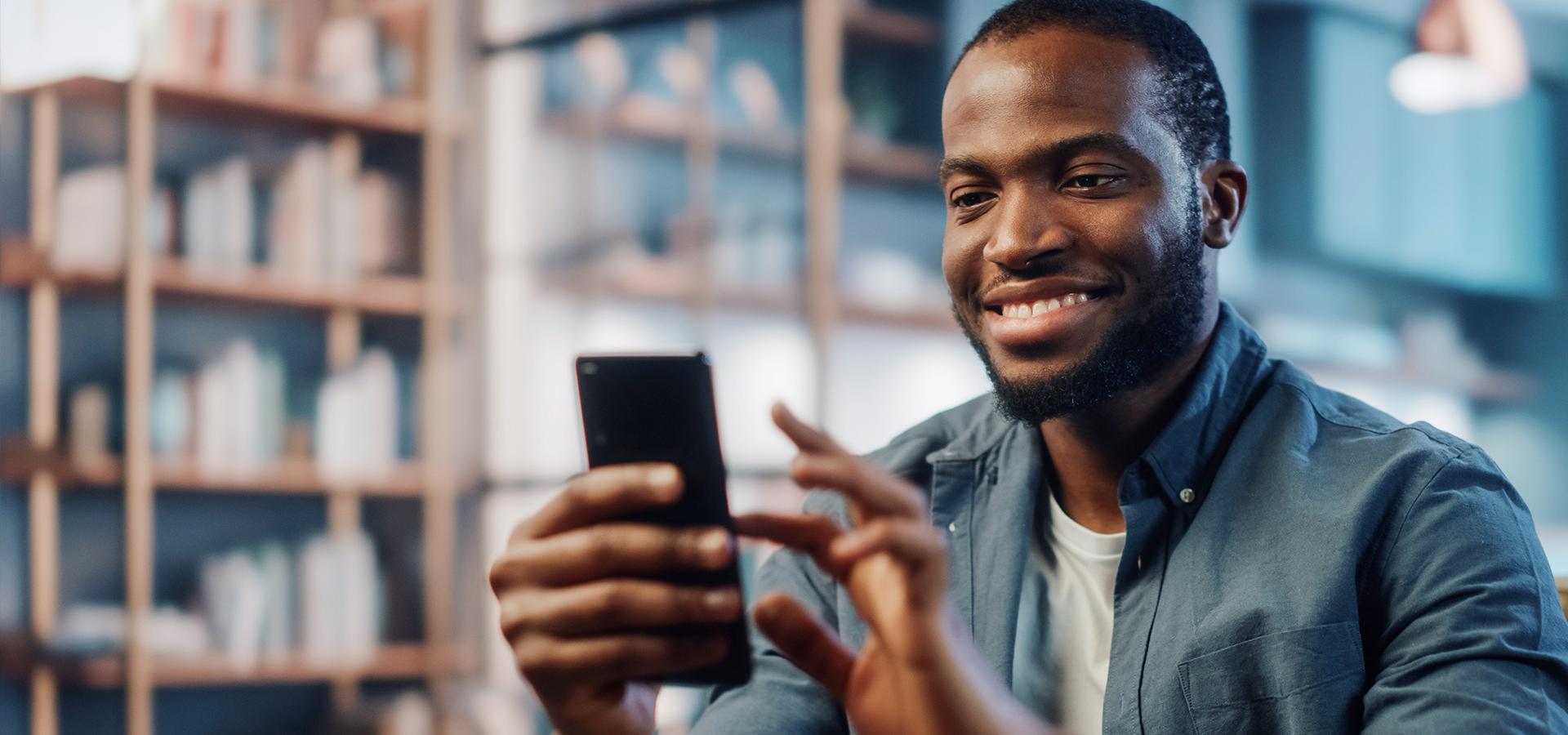 LINK Mobility - junger Mann sitzt zuhause im Wohnzimmer und tätigt einen Onlinekauf am Smartphone