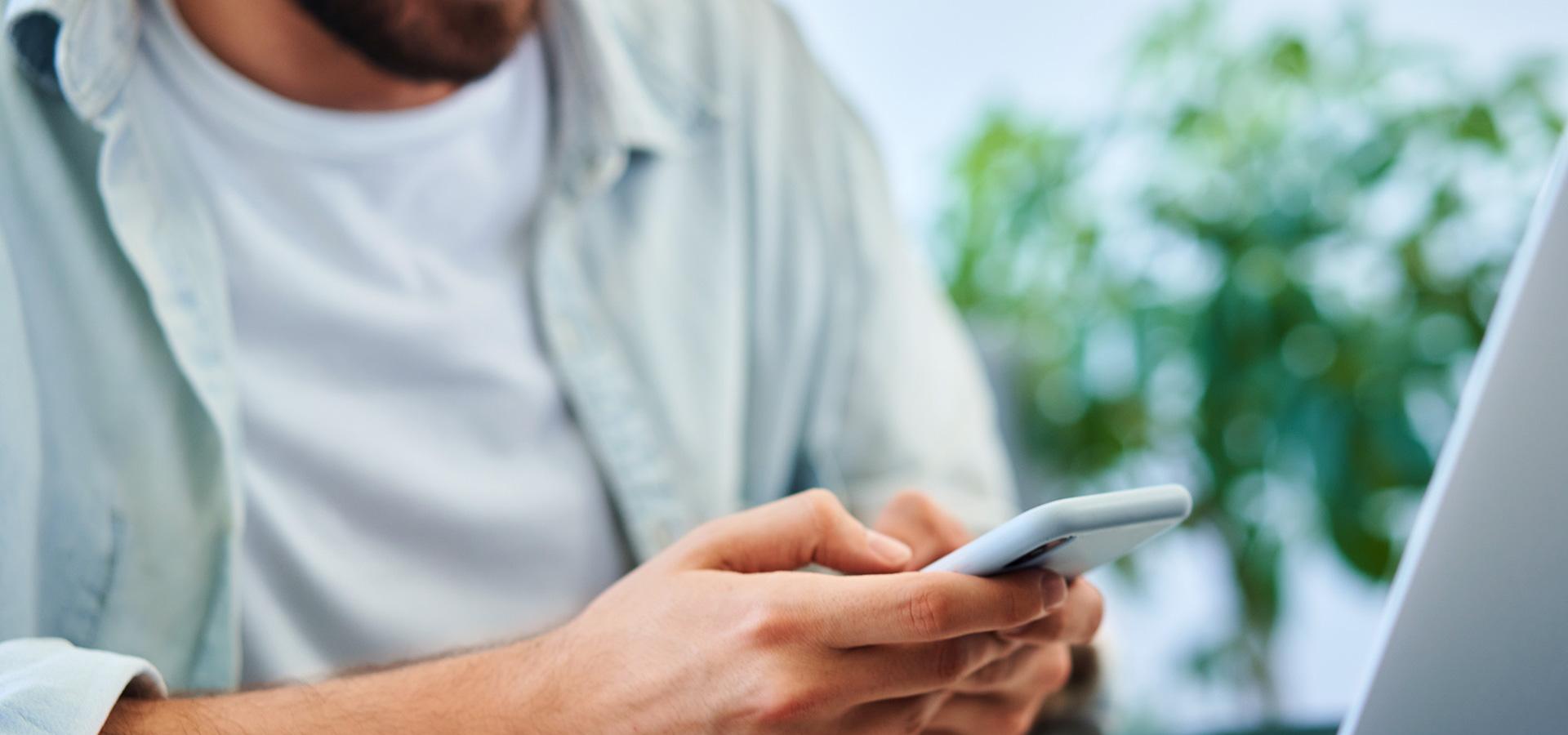 LINK Mobility - Junger Mann sitzt vor seinem Laptop und nutzt gleichzeitig sein Smartphone