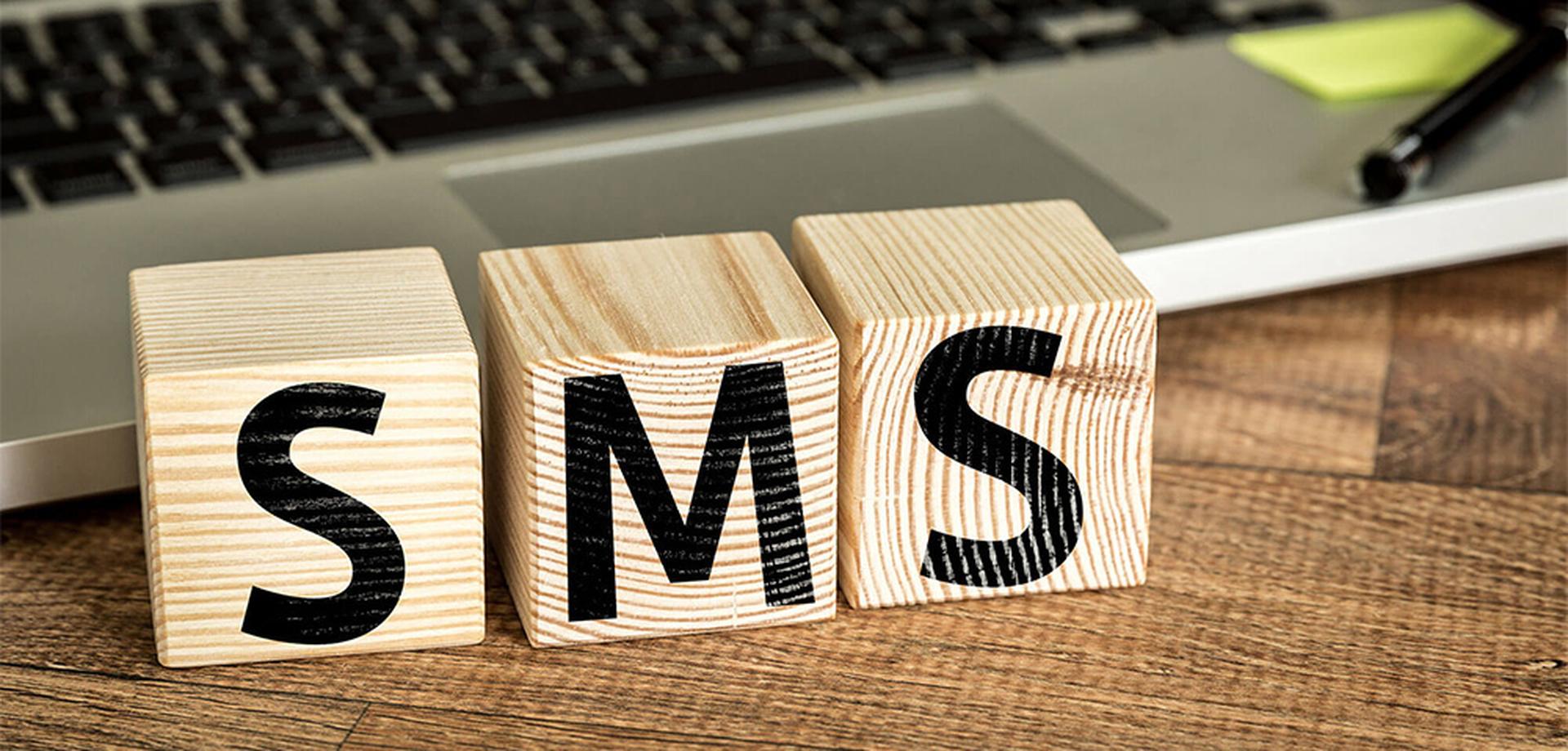 LINK Mobility -  SMS Buchstaben auf Holzblöcken