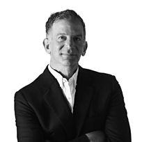 Black and white headshot of Brad Somberg crossing his arms.