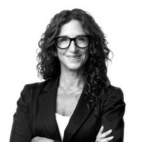 Black and white headshot of Ricki Pasinelli crossing her arms.