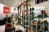 Long glass shelves held up by metal cables and rods have a variety of different athletic shoes on display. On the left of the shelves, the North Face logo is printed white on a red square hung up against a white wall.