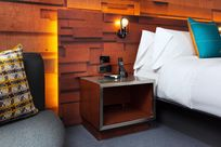 Interior of a bedroom. A bed with white pillows and bedsheets is placed next to a wooden night stand and gray sofa. The wall behind the room is decorated with Infused Veneer panels of different blocks of wood varying in size.