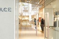Entrance of the Kit and Ace store. One of the two glass doors are open, revealing the interior of the shop. Wooden Fortina panels are used to line and decorate the top of the store as well as running vertically across the ceiling space of the shop.