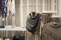 White Fortina panels run vertically along a wall of a store with shelves displaying various clothes. A wooden mannequin with a patterned gray shawl wrapped around it stands in front of the space.