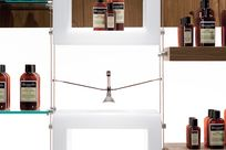 Multiple white cubic frames and glass/wooden shelves are hung up using cables and rods. On the shelves are various brown bottles.