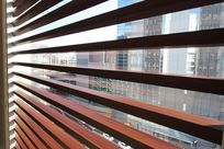 Maple Fortina panels are arranged horizontally across a window space, serving as blinds.