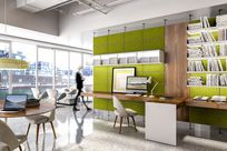 Green paneled Sorbetti shelves are placed to separate an office space into sections. Along the wall, white Sorbetti shelves are placed carrying various magazines and books. Wooden System 1224 shelves are also placed along the wall acting like a desk, paired with a white chair and monitor.