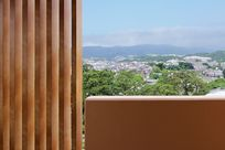Wooden Fortina panels stand in a line next to a brown rectangular wall, separating the floor from the ceiling. In between the wall and the ceiling is a view of the city.