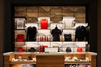 A dotted pattern making up mountains is printed on panels utilizing lit black System 1224 shelves displaying Planet13 merchandise.