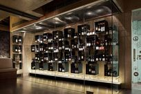 Various wine bottles are on display within black cubic frame shelves hung up by thin cables and rods. The shelves all are contained within a large glass display case.